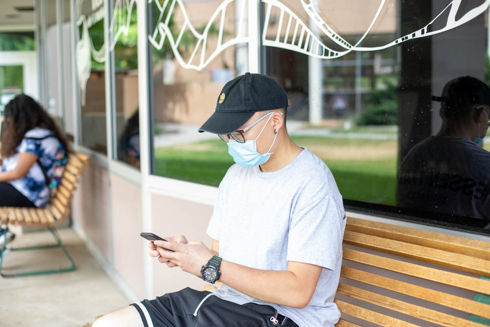 A student sitting on a bench outside Flix Cafe uses their phone to order a meal to-go.