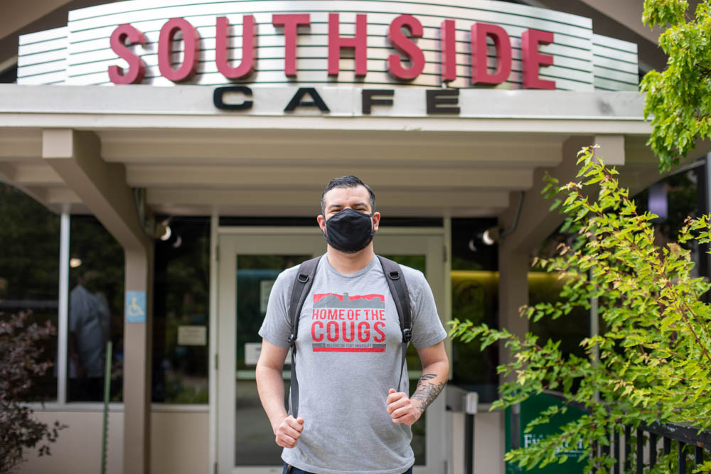 A student wearing a mask stands outside Southside Cafe.