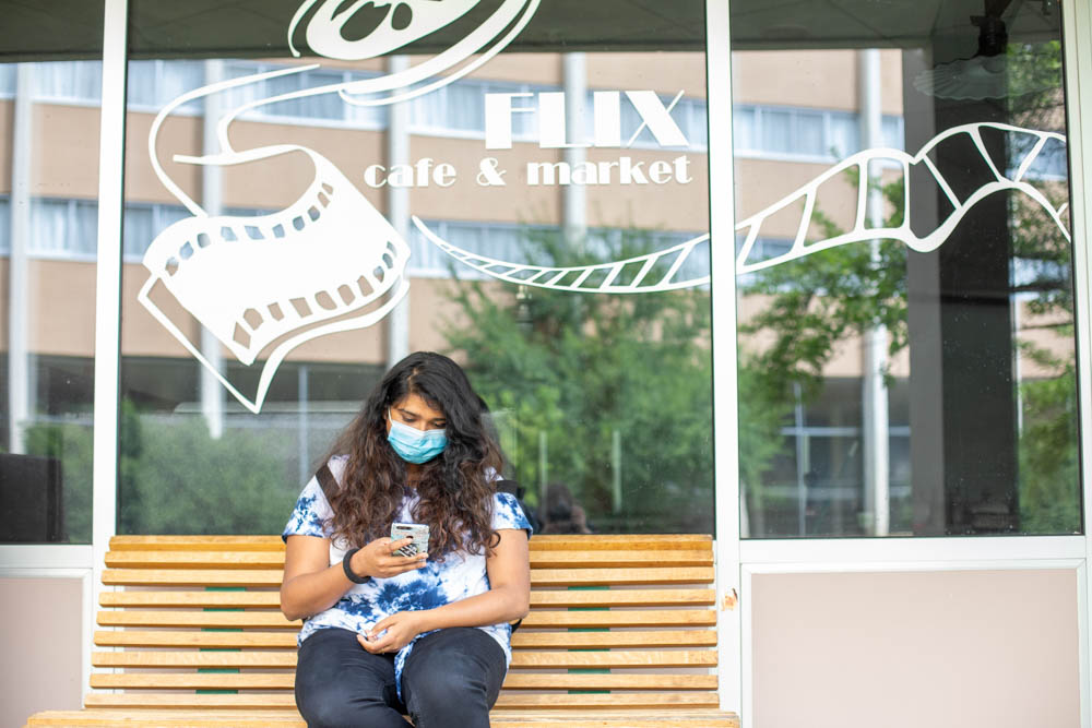 A student sits on a bench outside Flix Cafe and checks their phone.